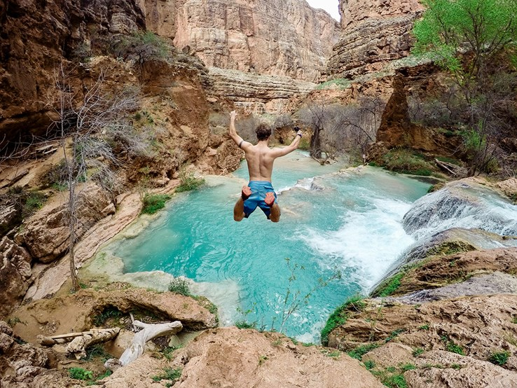 Man taking the plunge into the water in a canyon